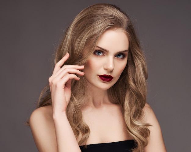 灰色の背景に笑みを浮かべて巻き毛の美しい髪の金髪女性。