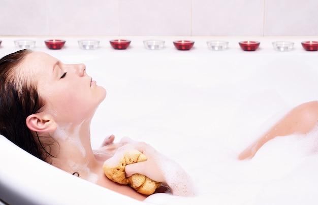 若い女性は浴槽の中で泡風呂を楽しんでいます。