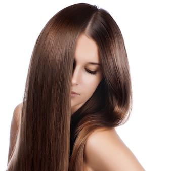 エレガントな長い光沢のある髪と美しい若い女性のクローズアップの肖像画