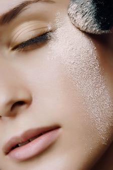 顔に粉体を持つ若い美しい女性