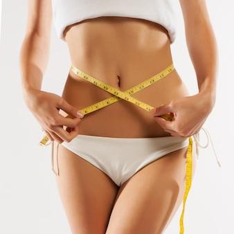 女性は彼女のウエストラインを測定します。完璧なスリムボディ