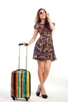 旅行スーツケース - 白い背景で隔離の側に立っているカジュアルな女性の完全な長さ