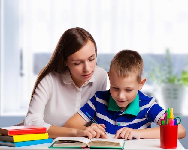 自宅でテーブルに座っている若い母親が学校からの宿題を彼女の小さな息子を助けて