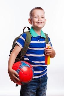 バックパック、ボール、白い背景で隔離の本と幸せな男子生徒