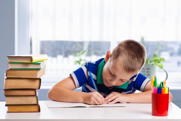 かわいい男子学生は白い背景で隔離の執筆です。