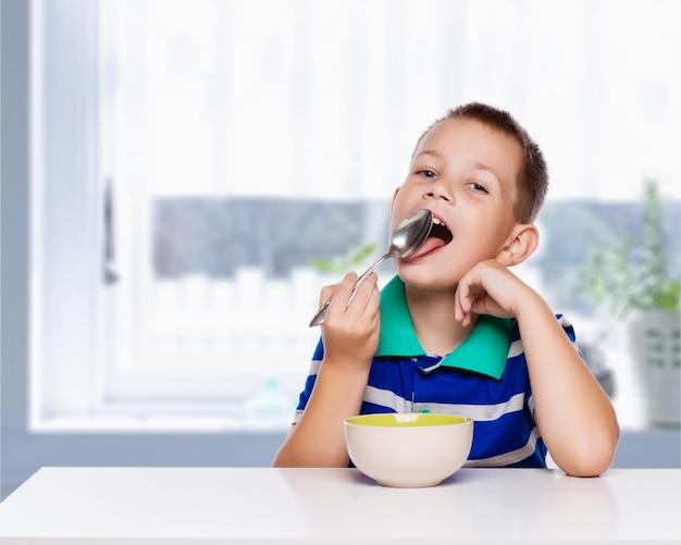 小さな男の子が台所で健康的な朝食を食べる
