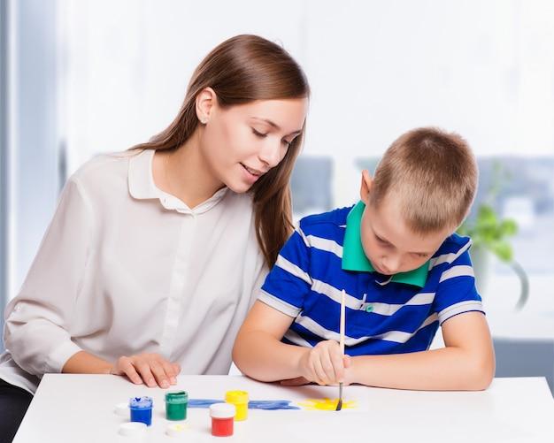 彼女の小さな息子を助ける家でテーブルに座っている若い母親