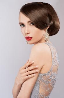 エレガントなヘアスタイルと官能的な美人の肖像画。完璧なメイク。