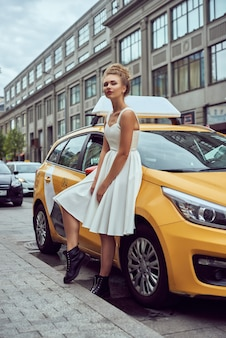 Белокурая девушка с развевающимися волосами на фоне улицы нью-йорка с такси.
