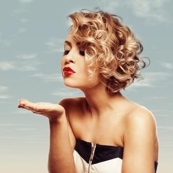 Молодая красивая блондинка дует поцеловал ее валентина