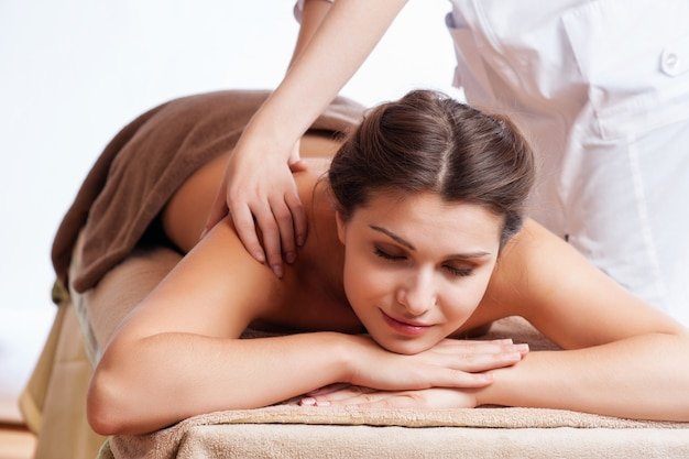 スパサロンで女性の体にマッサージをしているマッサージ師。美容治療のコンセプトです。