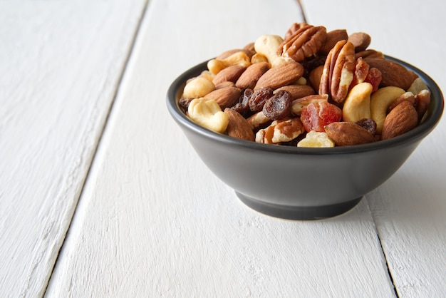 ボウルにナッツとドライフルーツを混ぜて、白く塗られた木の上に置きます。