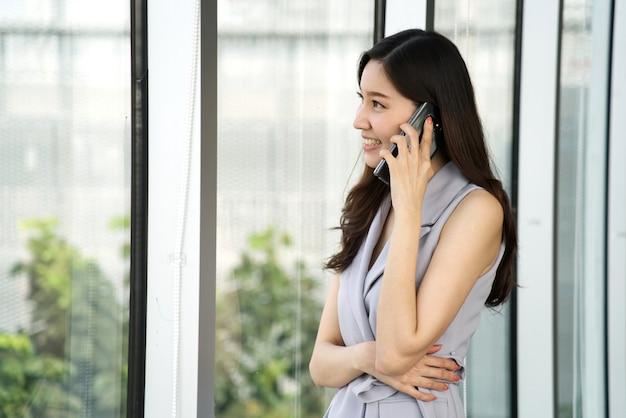 Дело азиатской умной красивой девушки говоря на мобильном телефоне стоя около окна в офисе.