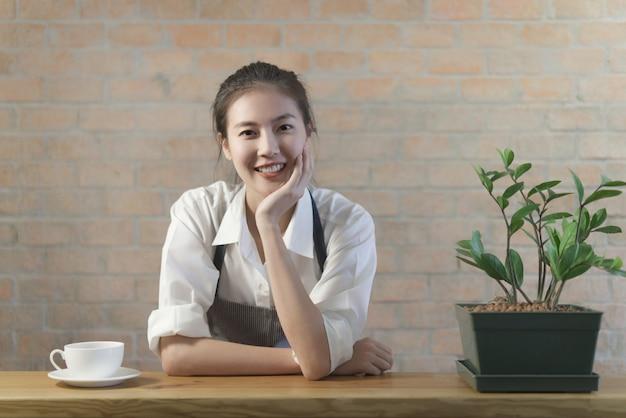 Стоящая молодая симпатичная азиатская девушка-бариста из кофе отдыхает на столе в баре