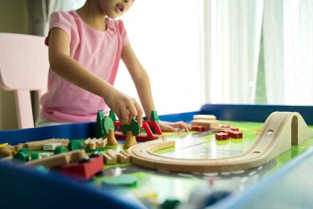 Молодой маленький азиатский милый ребенк играя деревянную игрушку на таблице дома.