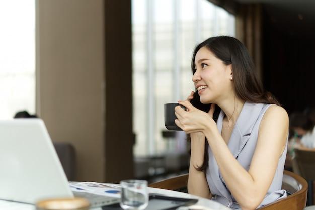 アジアのスマート美少女携帯電話でビジネスを話しているとコーヒーショップに座って一杯のコーヒーを保持しています。
