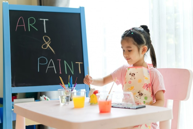 若いアジアの女の子が家で絵画クラスで動物の石膏人形をペイントします。