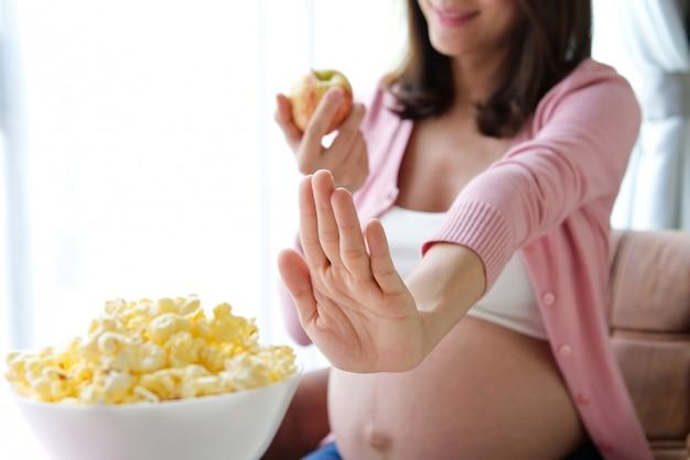 Диета беременности женщина отказывается от попкорна и выбирая красное яблоко.
