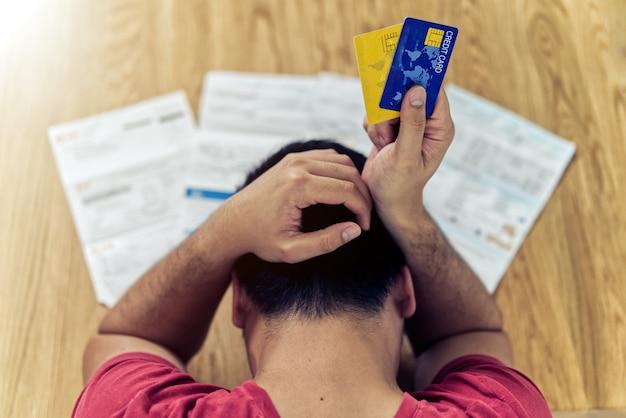 アジア人の男性がクレジットカードを保持しているとクレジットカードの負債とすべての手形を支払うためにお金を見つけることを考えて
