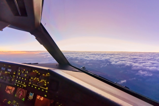 飛行機が空の雲の上の高高度で飛んでいるときに副操縦席で内部のコックピットからの眺め