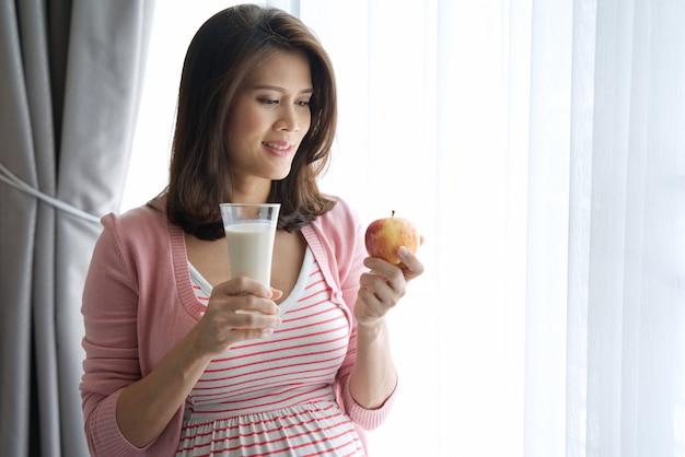Красивая молодая азиатская беременная женщина держа красное яблоко