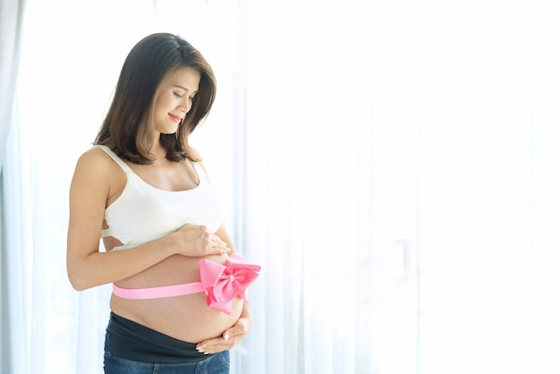 Вид сбоку красивых улыбающихся азиатских беременных женщин с большой розовой лентой на ее голом животике