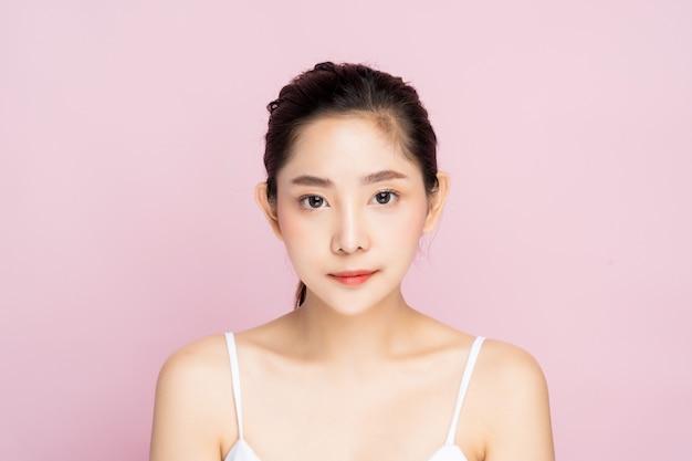 きれいな新鮮な白い肌に立って美しい若いアジア女性