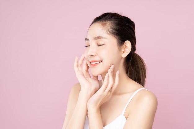 目を閉じて彼女自身の顔に触れる清潔で新鮮な白い肌を持つ若いアジア女性
