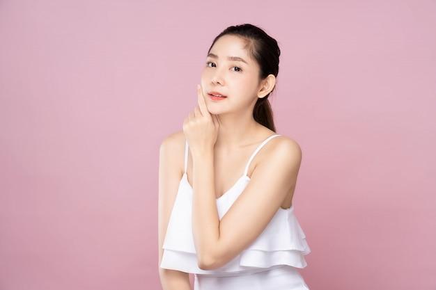 Молодая азиатская женщина с чистой свежей белой кожей, мягко касающейся своего лица в позе красоты