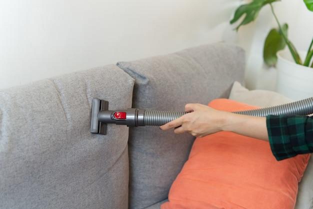 家政婦は、掃除機を使用してグレー色のソファを掃除しています。
