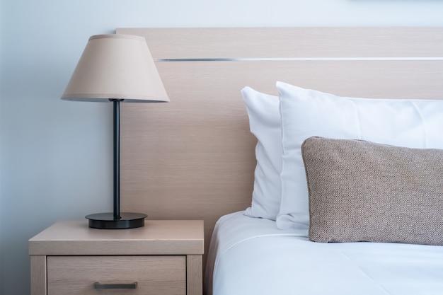 居心地の良いインテリアデザインの寝室のサイドテーブルにテーブルランプとベッドヘッドのトリミングショット。