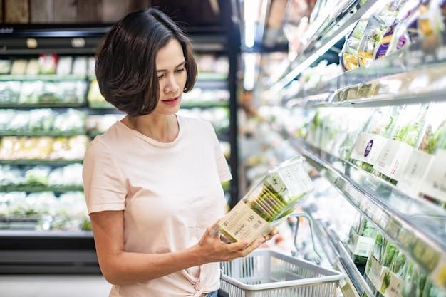 スーパーマーケットを歩いて、サラダの箱を持って食料品バスケットを保持している若いアジアの美しい女性。