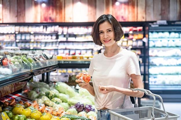Молодая азиатская красивая женщина держа продуктовую корзину идя в супермаркет, держа томат в зоне овоща и плодоовощ с улыбкой.