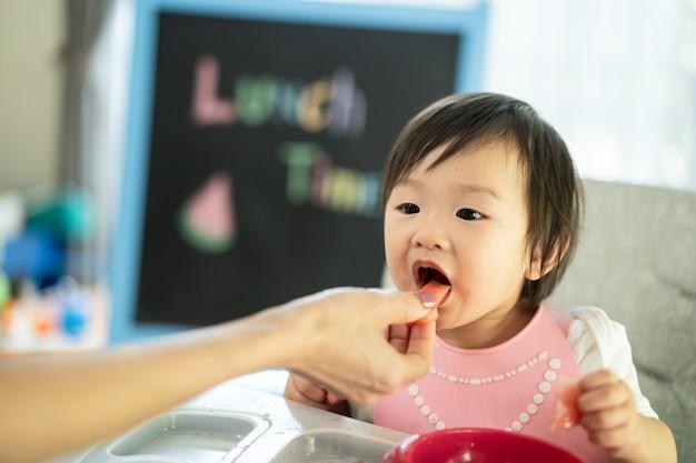 自宅で赤ちゃんの高い椅子給餌席で若いかわいい子供にスイカを食べている母親は、食事を楽しみ、甘い果物を食べるために口を開けます。