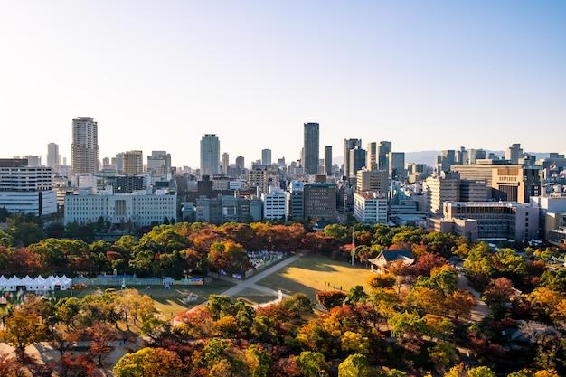 昼間の大阪城の屋上からの美しい大阪市街の眺め。メープルレッドは、城の周りの公園で秋のシーズンを葉します。