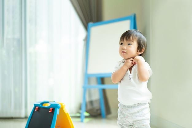 アジアのかわいい子供が自宅で立っておもちゃを遊んで、脇を見て、何をするかについて質問します。