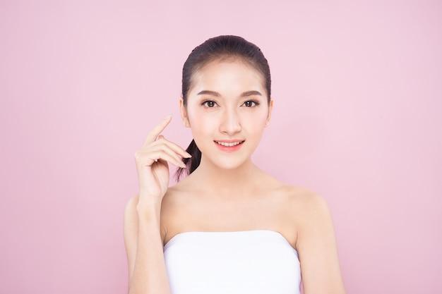 Красивая молодая азиатская женщина с чистой свежей белой кожей касаясь ее собственному лицу мягко в представлении красоты.