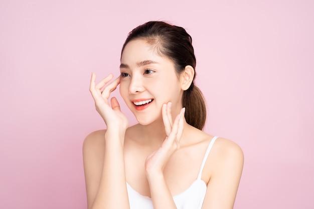 Красивая молодая азиатская женщина с чистой свежей белой кожей касаясь ее собственному лицу мягко в представлении красоты касаясь с пальцами в розовой предпосылке.
