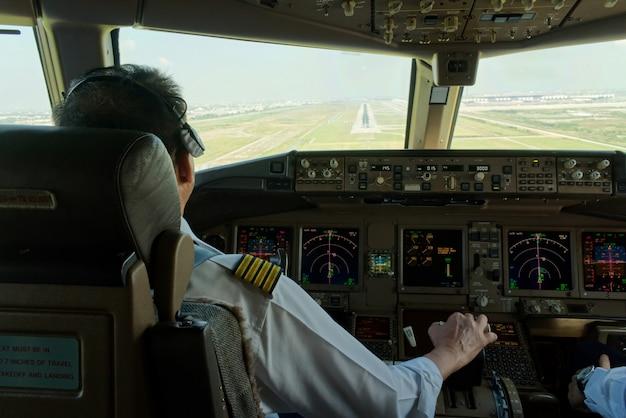 Капитан авиалайнера летит самолетом к взлетно-посадочной полосе.