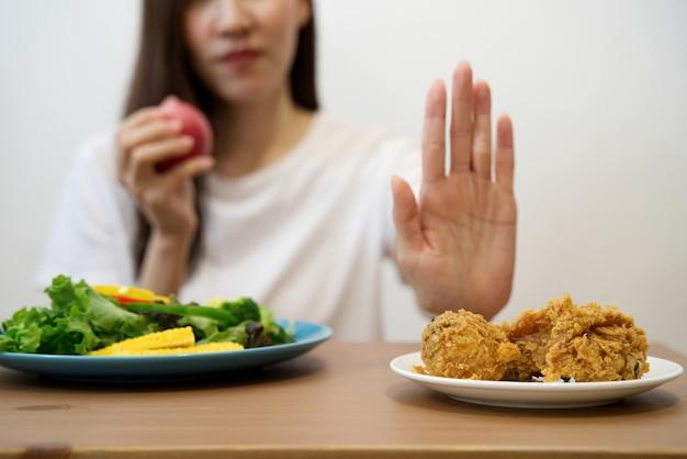 Крупным планом женщина, используя руку отвергать нездоровую пищу, выталкивая ее любимую жареную курицу.