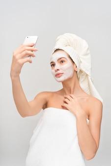 白い粘土の顔のマスクを持つ美しい若い女性