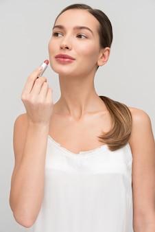 美しい若い女性は化粧を施すこと