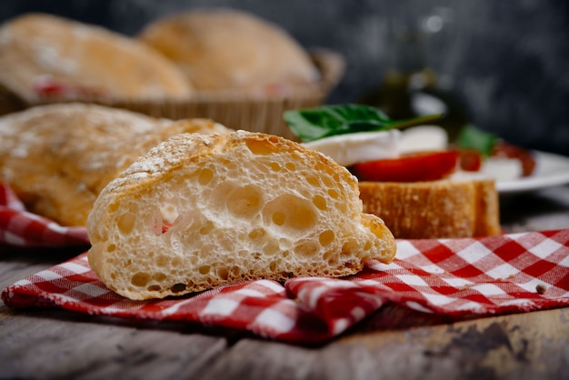 Традиционный итальянский хлеб чиабатта с зеленью как крупный план на клетчатой салфетке
