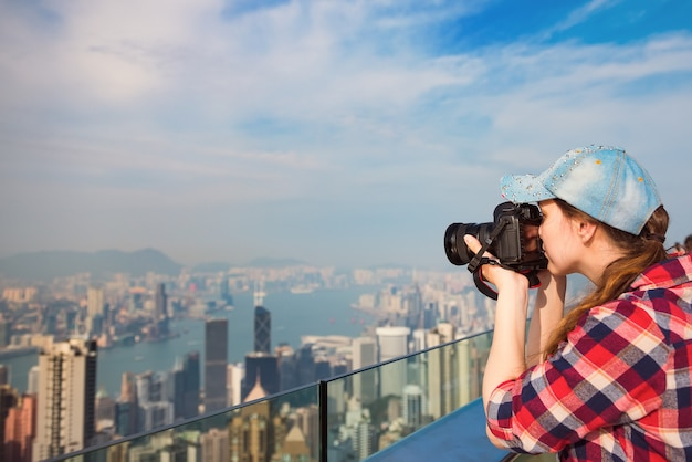 Молодая женщина фотографирует гонконг с пика виктория. туризм, отдых, путешествия концепция.