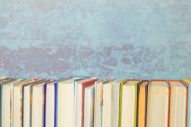本棚、青い背景、ビンテージトーンの本。教育、学校のテーマに戻る。