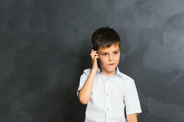 電話、小さなボスで話している白いシャツの少年