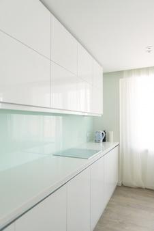 ミニマリストスタイルの白いキッチン。インテリア、デザインのテーマ