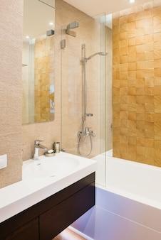 暖かい色調の垂直のゲスト用浴室。