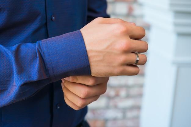 彼の青紫のシャツの袖にボタンを押す男
