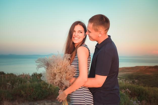 海と空の背景に対してランデブーに幸せなカップルの男女